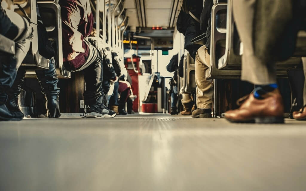 Foto do chão de um ônibus onde é possível ver os pés das pessoas sentadas.